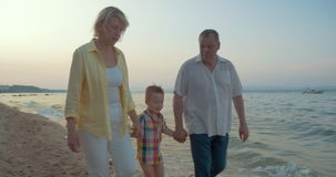 Grandparents and little grandchild walking on the beach stock video