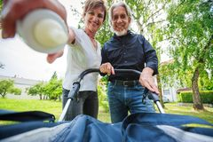 Grandparents Looking At Their Grandchild. In baby stroller, POV Stock Photo