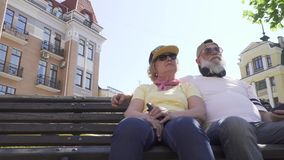 Grandparents in modern clothes and accessories relaxing on bench in the city. Modern grandparents are relaxing on the bench in park. Lovely granny and granddad stock footage