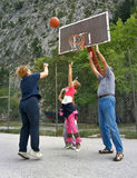 Grandparents play basketball. Grandmother and grandfather play basketball with the grandchildren Stock Image