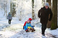 Grandparents playing with grandchildren in winter forest royalty free stock image