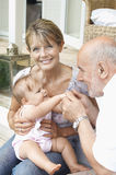 Grandparents Playing With Granddaughter On Porch Royalty Free Stock Photo