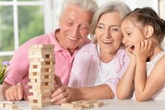 Grandparents playing with her little granddaughter. Portrait of grandparents playing with her little granddaughter stock photos