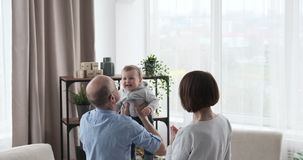 Grandparents lifting up cute baby girl into the air stock footage