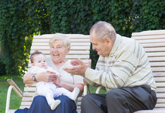 Grandparents playing with a little baby in the garden. On sunny day Stock Image