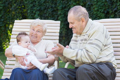 Free Grandparents Playing With A Little Baby In The Garden Royalty Free Stock Images - 27650619
