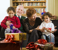 Grandparents and presents. Grandparents giving presents to grandchildren on an holiday Stock Photo