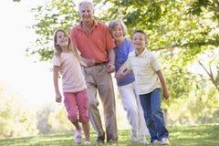 Grandparents que andam com netos Imagens de Stock