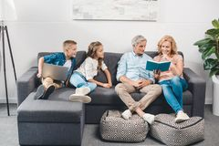 Family with book and laptop royalty free stock photography