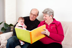 Grandparents reading book to baby girl. Proud and happy grandparents reading book to educate their grandchild. Baby girl enjoying book while sitting on couch in stock photo