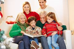Grandparents reading book to grandchildren. At christmas Stock Photos