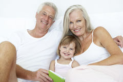 Grandparents Reading To Granddaughter In Bed Royalty Free Stock Photo