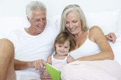 Grandparents reading to granddaughter in bed Stock Image