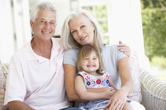 Grandparents Relaxing On Seat With Granddaughter Stock Photo