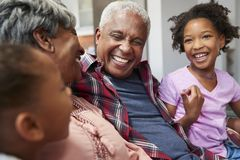 Grandparents Relaxing On Sofa At Home With Granddaughters royalty free stock image
