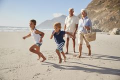 Grandparents Running Along Beach With Grandchildren royalty free stock images
