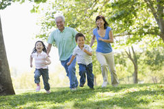 Grandparents running with grandchildren Royalty Free Stock Image