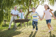 Grandparents Serving Grandchildren At Family Barbeque Stock Photos