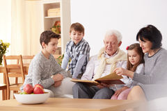 Grandparents showing photo album to grandchildren. Grandparents showing family photo album to interested grandchildren royalty free stock photos