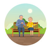 Grandparents are sitting on bench in park, smiling and speaking. Stock Images