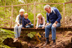 Grandparents sitting with grandkids on a bridge in a forest Royalty Free Stock Image