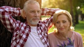 Grandparents sitting in park near tree and enjoying romantic date love and trust. Grandparents sitting in park near tree and enjoying tic date love and trust stock image