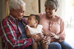 Grandparents Sitting On Sofa With Baby Granddaughter At Home stock photos