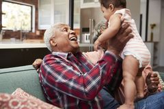 Grandparents Sitting On Sofa Playing With Baby Granddaughter At Home royalty free stock image