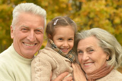 Grandparents smiling with granddaughter. Relaxing in autumn forest Stock Photo