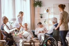 Grandparents spending time in common room with their caregivers stock images