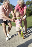 Grandparents Teaching Granddaughter To Ride Scooter In Park Royalty Free Stock Images