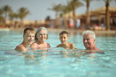 Grandparents with their grandchildren. Happy grandparents with their grandchildren in pool on vacation royalty free stock photography