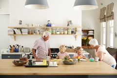 Grandparents and their grandkids talking in the kitchen stock image