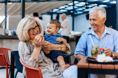 Grandparents With Their Grandson At Cafe. Grandparents With Their Grandson Spending Lovely Time At Cafe Royalty Free Stock Photo