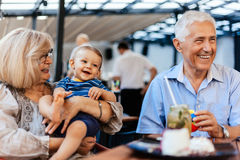 Grandparents With Their Grandson At Cafe. Grandparents With Their Grandson Spending Lovely Time At Cafe Royalty Free Stock Photography