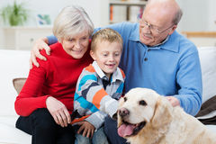 Grandparents with their grandson and pet retriever. Grandparent s with their young grandson and loyal golden retriever dog sitting together in the living room as Stock Photography