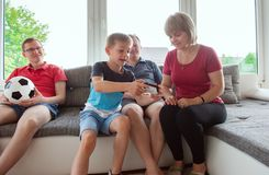 Grandparents, their son and grandson are playing computer game. Emotionally at home on sofa royalty free stock photo