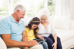 Grandparents using tablet with their granddaughter Royalty Free Stock Images