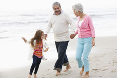 Grandparents Walking Along Beach With Granddaughter Stock Images