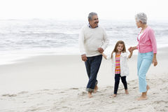 Grandparents Walking Along Beach With Granddaughter Royalty Free Stock Photos