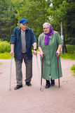 Grandparents walking with crutches. Elderly men and women walking with canes Royalty Free Stock Photo