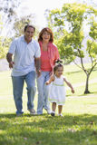 Grandparents walking in park with granddaughter Stock Photo