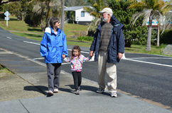 Grandparents walking with their granddaughter Stock Images