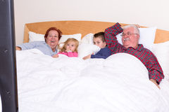 Grandparents Watching TV in the bed with their Grand kids. They look excited, perhaps its an adventure movie Royalty Free Stock Photos