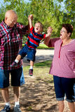 GrandparentsLiftGrandson. A grandpa and grandma lift their grandson into the air. Grandma is looking at her grandchild with a face as if she is making sound Stock Image