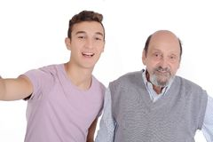 Grandpther and their teen grandson taking a selfie. Grandfather and their teen grandson taking a selfie. Isolated on white background Stock Photography