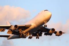 Grands avions de cargaison approchant l'aéroport au coucher du soleil Images libres de droits