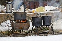 Grands bacs pour faire cuire au-dessus d'un incendie ouvert à l'extérieur pendant l'hiver Photographie stock