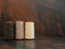 Grands cônes industriels des fils de couture blancs et bruns s'étendant et se tenant sur un fond foncé Tir de studio de vue de fa photo libre de droits
