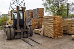 Grands chariot élévateur et piles de nouveaux conseils en bois et goujons au Th photos stock